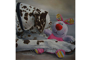 A liver spotted Dalmatian cuddles a toy